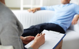 Psychologist making notes during psychological therapy session